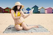 stock photo of beach hut  - Young woman sitting at coast while wearing bikini and using sunscreen with the background of the beach huts - JPG