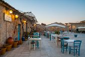 picture of early morning  - early morning in the main square of Marzamemi a small sicilian fishing village with some wooden tables and chairs of a typical restaurant - JPG