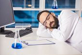 picture of workplace safety  - Handsome male scientist sleeping in safety glasses at his workplace in a laboratory - JPG