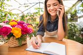 picture of flower shop  - Portrait of young female florist talking on phone and making notes at flower shop - JPG