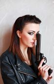 picture of straight jacket  - Beautiful woman holding a pistol looking straight to camera