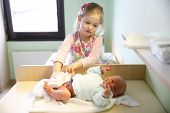 foto of sisters  - Newly made sister with her newborn brother in hospital maternity ward just before leaving for home - JPG