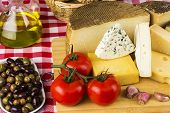 picture of cheese platter  - Assorted cheese olives tomatoes and other ingredients typical of the Mediterranean diet - JPG