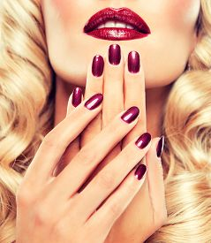 stock photo of lipstick  - Blonde model with curly Perm hair with Burgundy nails and lipstick - JPG