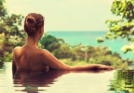 stock photo of sunbathers  - Beautiful tanned girl admires the landscape and rests in the swimming pool - JPG