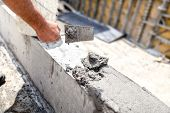 Construction Worker Leveling Concrete With Putty Knife At Building Site. poster