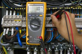 picture of electricity meter  - Electrician performing voltage measurements with electrical multimeter - JPG
