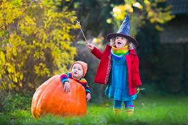 stock photo of jack o lanterns  - Little girl in witch costume and baby boy in huge pumpkin playing in autumn park - JPG