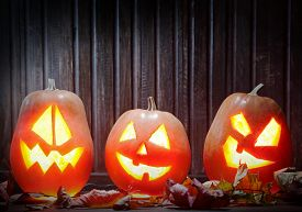 picture of jack o lanterns  - Jack o lanterns Halloween pumpkin face on wooden background and autumn leafs - JPG