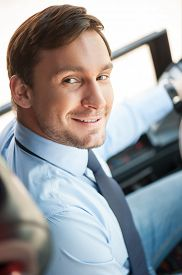 image of steers  - Attractive bus driver is sitting at steering wheel of the vehicle - JPG