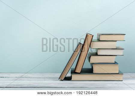 poster of Stack of colorful books. Education background. Back to school. Book, hardback colorful books on wooden table. Education business concept. Copy space for text