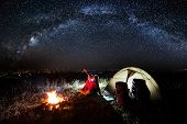 Night Camping Near The Town. Young Couple Sitting Near Campfire And Tent, Looking At Beautiful Night poster
