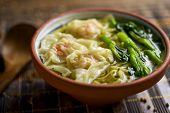 closeup of an earthenware bowl with shrimp wonton noodle soup with choy sum, placed on a table set f poster