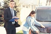 Loss adjuster and young woman inspecting car after accident poster