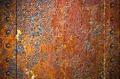 Textura de metal enferrujada com rebites sobre fundo vermelho