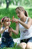 Mutter und Tochter in Jeans mit Spielzeug im freien