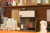 pic of mud pack  - coffee machine on counter with cups next to it and alcohol bottles on the shelve - JPG