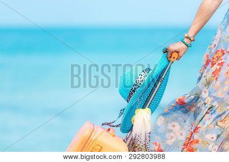 poster of Travel Plan. Hand Women Traveler Holding Orange Luggage Walking On The Beach.  Traveler And Tourism