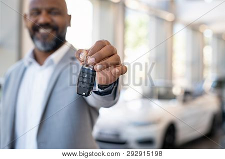 poster of Smiling salesman holding new car keys in car showroom. Businessman is suit showroom showing car keys