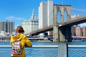 Happy Young Woman Tourist Sightseeing By Brooklyn Bridge, New York City, At Sunny Spring Day. Female poster