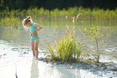 Young Girl Taking Healing Mud Baths On Lake Gela Near Vilnius, Lithuania. Child Having Fun With Mud. poster