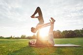Balancing Yoga Poses. Healthy And Young Couple Practicing Acro Yoga Together In The Morning Park. Ma poster