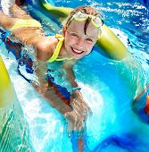 foto of amusement park rides  - Child on water slide at aquapark - JPG