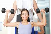 Gym fitness people - woman lifting weights with help from instructor and fitness trainer in gym. Bea