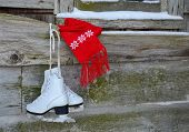 stock photo of red siding  - Ice skates and red winter scarf hanging on old barn - JPG