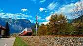 Red Blue Train In Motion In Austrian Alps Mountains. High Speed Mountain Train Arrives At Hallstatt  poster