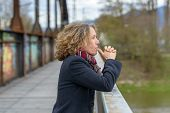 Thoughtful Woman Gazing Out From The Railing Of A Bridge With Her Thumbs To Her Mouth And A Serious  poster
