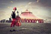 pic of cello  - Young man in funny clothes holding a cello with circus in the background - JPG