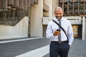 Satisfied african businessman using smartphone while walking in the street. Mature smiling business  poster