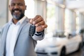 Smiling salesman holding new car keys in car showroom. Businessman is suit showroom showing car keys poster