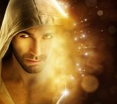 Fantastical portrait of a handsome hero type man in hooded garment in dazzling background with rays