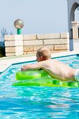 Young Man Is Swimming With Air Mattress In Pool
