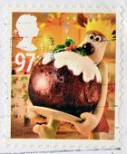 a stamp printed in Great Britain shows image of Gromit with Christmas pudding