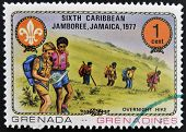 GRENADA - CIRCA 1977: A stamp printed in Grenada dedicated to the Boy Scouts shows overnight hike ci