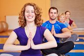 Happy woman smiling in yoga class in a fitness center