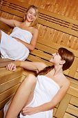 Two smiling women talking in a sauna