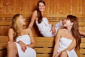 Three happy women sitting and talking in a sauna