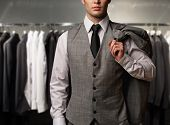 stock photo of wardrobe  - Businessman in classic vest against row of suits in shop - JPG