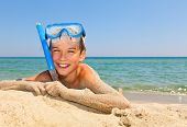 Happy boy wearing snorkeling gear relaxing on the beach