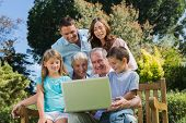 Smiling multi generation family with a laptop sitting in park on a bench