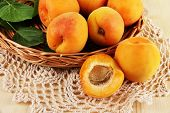 Apricots on wicker coasters on napkin on  wooden table