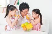 Asian family drinking orange juice. Happy Asian grandparent and grandchildren enjoying cup of fresh squeeze fruit juice at home. Healthcare concept.