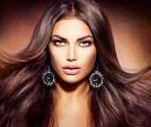 Glamour Beautiful Woman with Beauty Brown Hair. Blowing Long and Healthy Hair. Professional Make up.