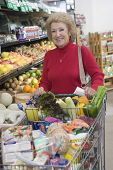 Portrait of a smiling mature woman doing grocery shopping in supermarket