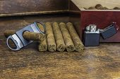 stock photo of tobacco smoke  - A group of cigars layed out on an old desk waiting to be cut and smoked - JPG