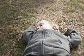 Closeup of a boy taking a nap on grass